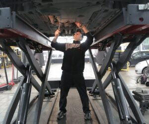 Mechanic works on under carriage of car